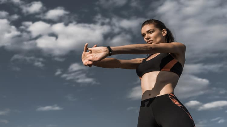 Sporty woman stretching her forearms