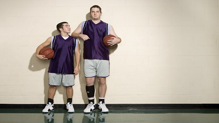 A tall and short basketball player stood side by side