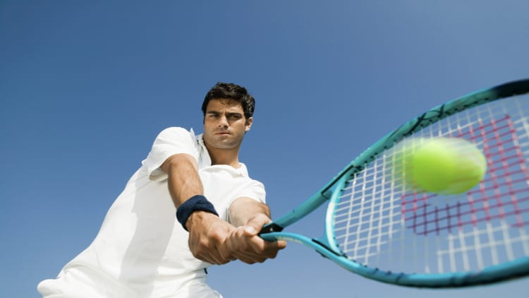 Tennis player hitting the ball with his racket