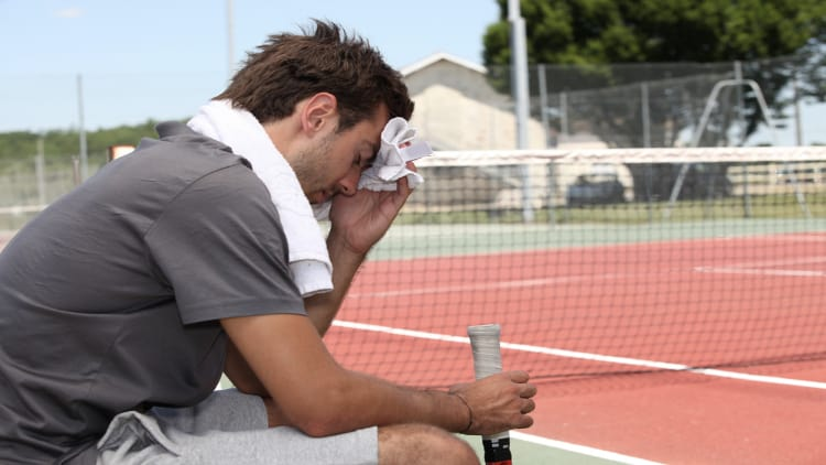 Tired tennis player holding a sweat toewl to his head