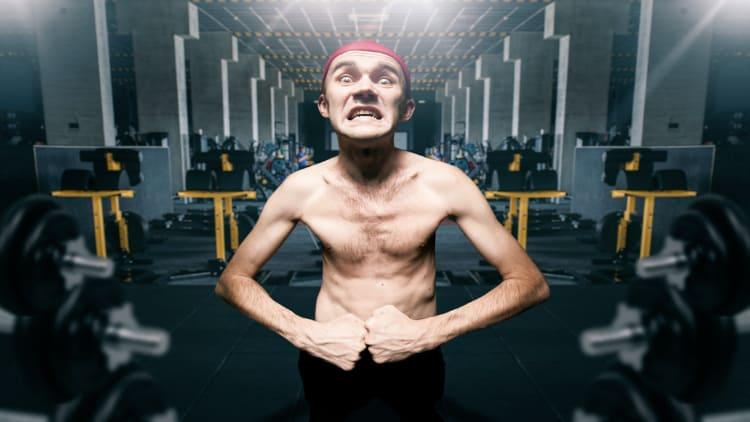 Skinny man flexing his muscles