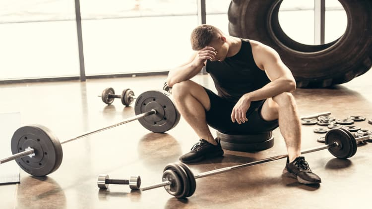 Upset man sat in gym next to barbells and dumbbells
