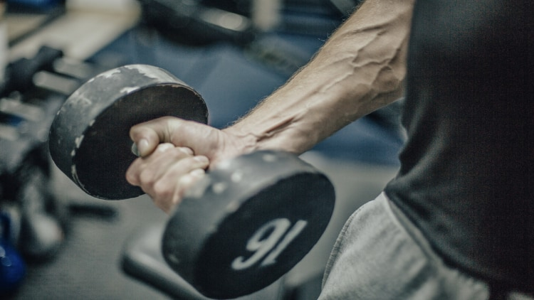 A vascular arm holding a dumbbell in the gym