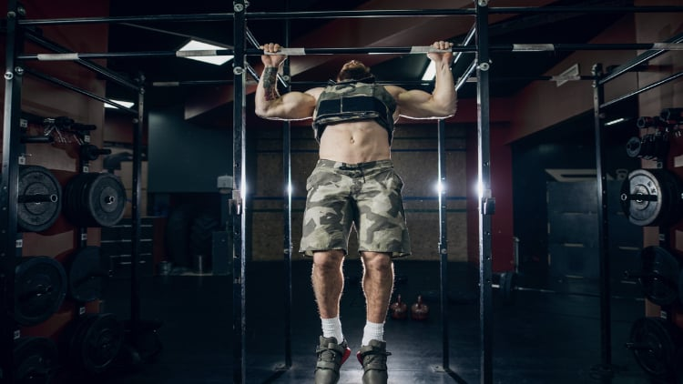 Man performing pull ups in a weighted vest