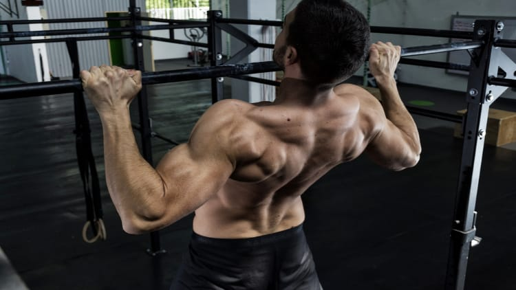 Man doing wide grip overhand pull ups