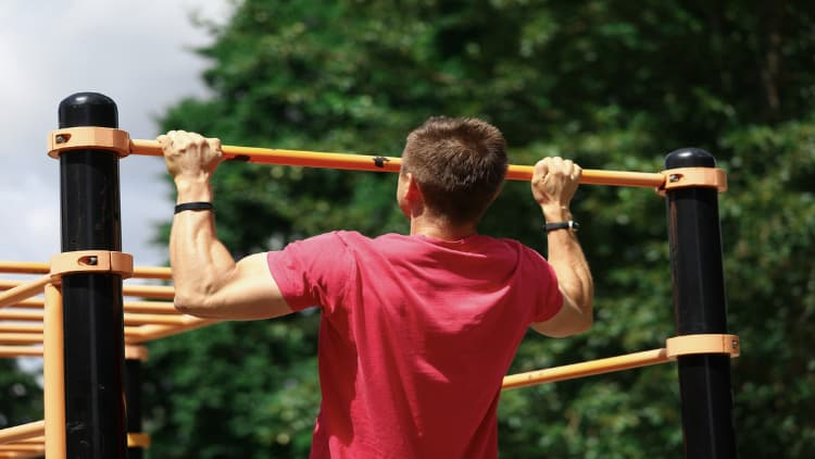 Man performing wide grip pull ups in the park