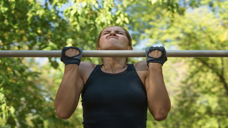 Woman doing chin ups in the park