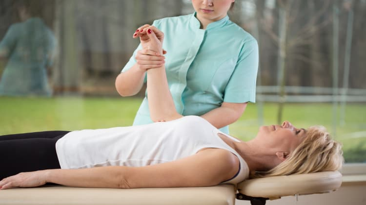 Physiotherapist performing forearm rehabilitation on a patient