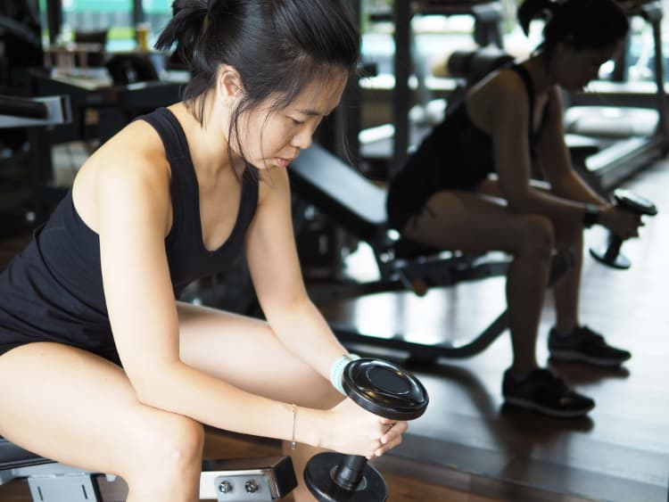 Asian lady holding a dumbbell