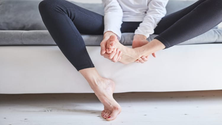 Woman sat on the sofa holding her foot