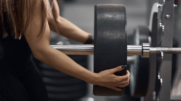 Woman loading bumper plate onto a barbell