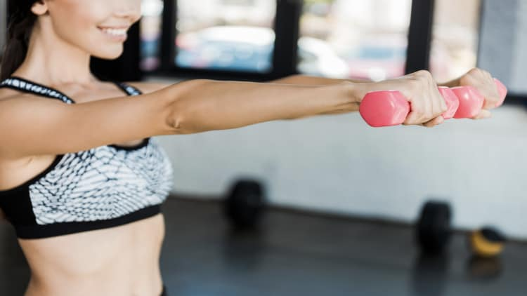 Woman holding pink dumbbells