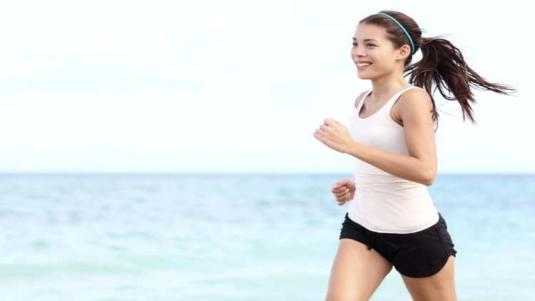 Smiling woman jogging on the beach