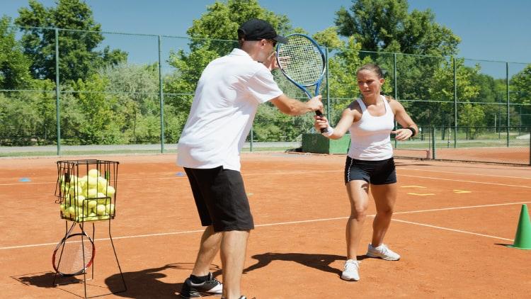 Woman having a tennis lesson