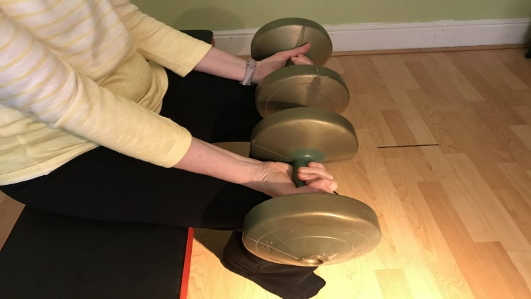 Lady doing wrist curls with dumbbells