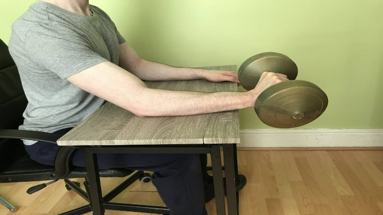 Man doing a dumbbell wrist extension over a desk