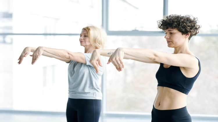 Two women stretching their wrist extensors
