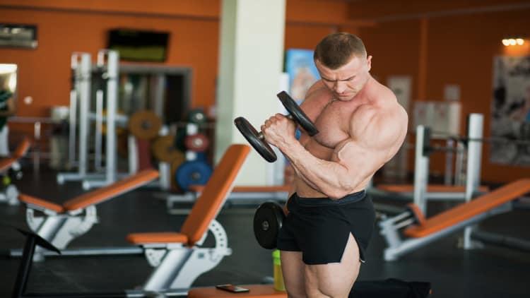 Bodybuilder doing standing alternating hammer curls