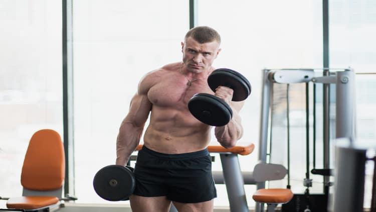 Bodybuilder performing alternating hammer curls at the gym