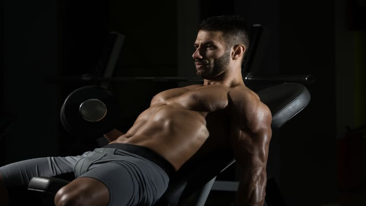 Bodybuilder performing alternating incline dumbbell curls during his gym session