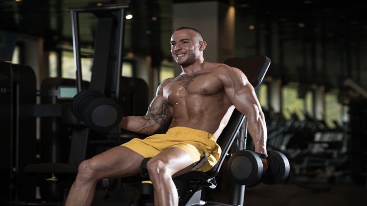 Bodybuilder performing alternating incline dumbbell curls