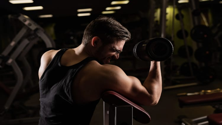 Man squeezing his bicep during a set of one arm dumbbell preacher curls