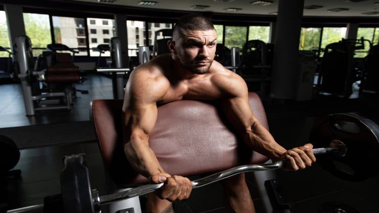 Athletic man doing preacher curls with an EZ bar during his gym workout