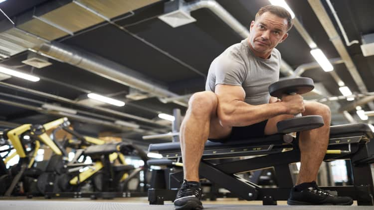 Man performing a concentration hammer curls at the gym