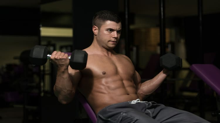 Muscular man doing incline curls at the gym