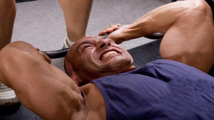 Intense bodybuilder doing a skull crusher for his triceps