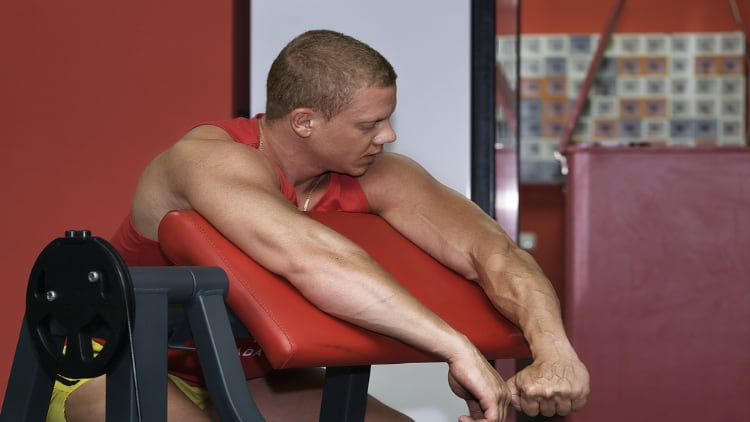 Man resting at the preacher curl station during his workout