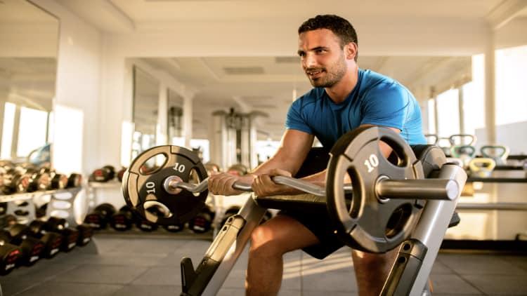 Man doing narrow grip preacher curls at the gym