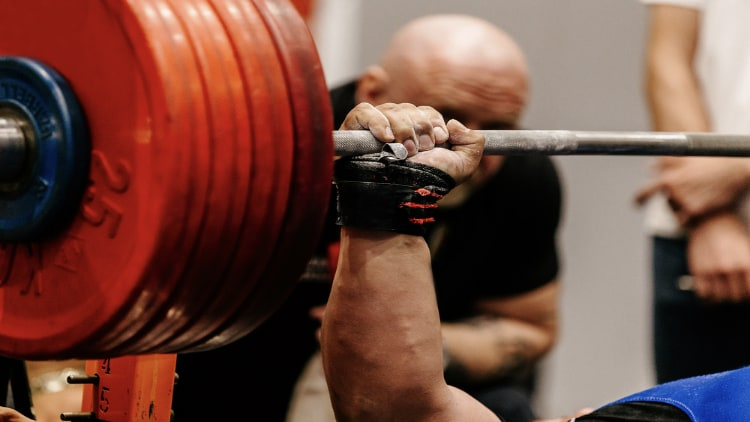 Powerlifter gripping the barbell during his bench press attempt at a powerlifting meet