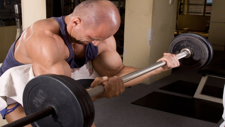 Muscular man performing a straight bar preacher curl at the gym