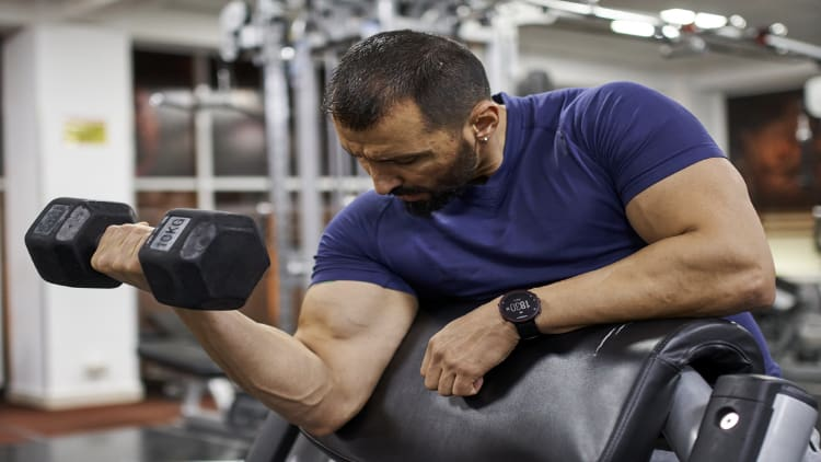 Bodybuilder performing single arm preacher curls during a gym workout