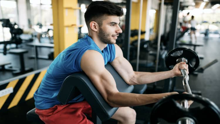 Side view of an athletic man performing EZ bar preacher curls at the gym