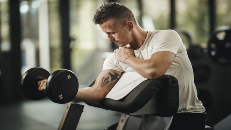 Man doing a single arm dumbbell preacher curl at the gym