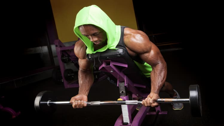 Bodybuilder doing the EZ bar spider curl exercise for his biceps
