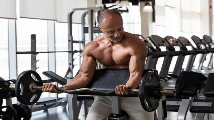 Man performing wide grip preacher curls at the gym