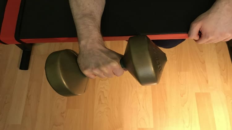 A man doing a dumbbell wrist extension over a bench