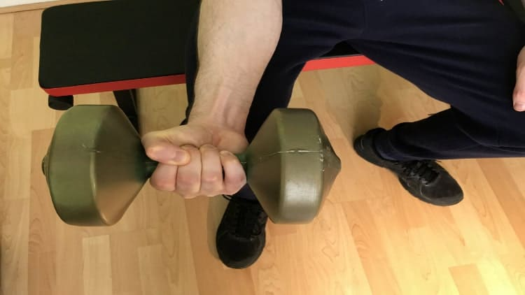 A man doing a dumbbell wrist flexion over his knee