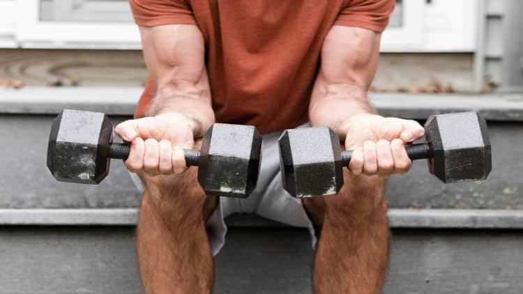 Man doing the dumbbell wrist flexion exercise
