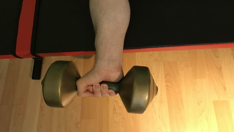 Man doing the dumbbell wrist flexion over a bench