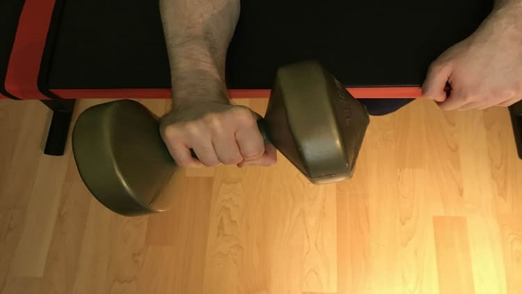 A man doing a palm down dumbbell wrist curl