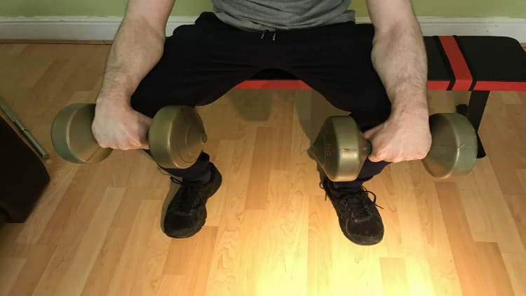 Man resting the dumbbells on his legs