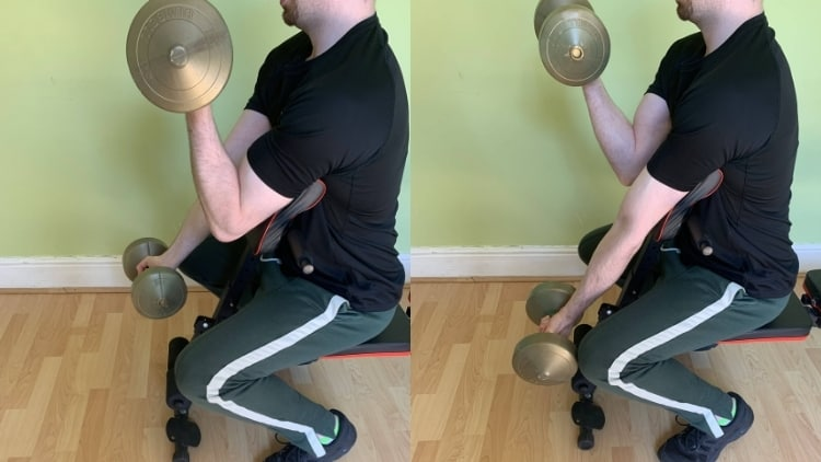 A man performing alternating preacher curls with dumbbells