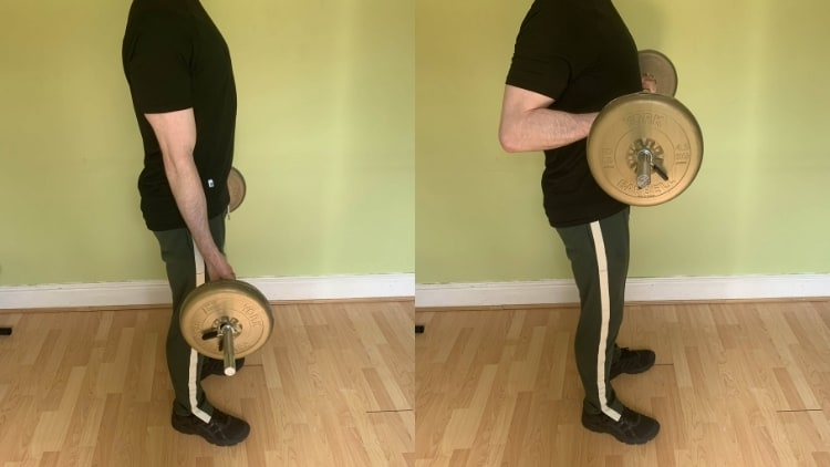 A man performing a barbell drag curl for his biceps