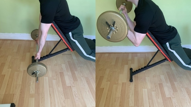 A man doing a barbell spider curl for his biceps