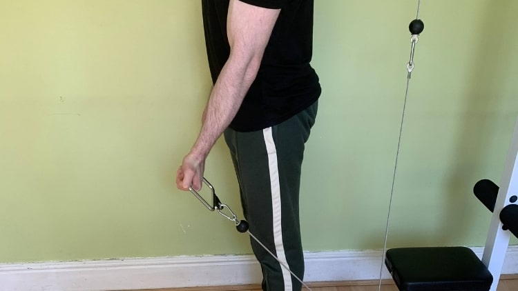 A common mistake during the behind body cable curl, holding the handle too far out in front