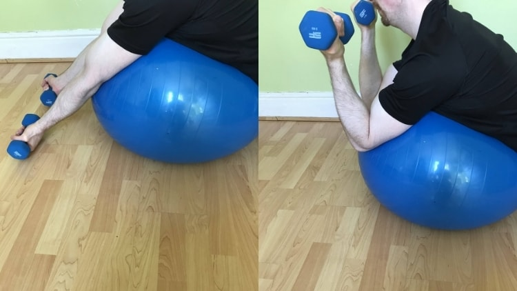 A man doing bicep exercises on an exercise ball